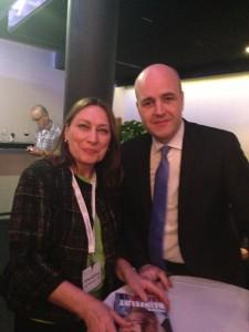 """Irina Gainza, VD för IGS Assistans AB, poserar tillsammans med Fredrik Reinfeldt, Sveriges fd statsminister, efter att hon fått ett signerad exemplar av """"Halvvägs"""". Foto: Alexis Gainza."""